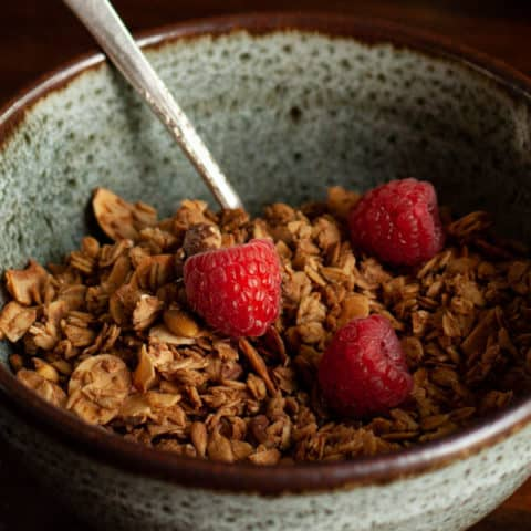 Granola in blue speckled pottery bowl with raspberries on top