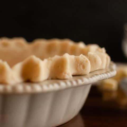 Flaky Gluten Free Pie crust in ceramic pie dish with dark background