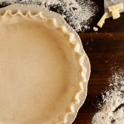 Prepared and crimped gluten free pie crust in ceramic dish surrounded by butter and flour on wooden surface