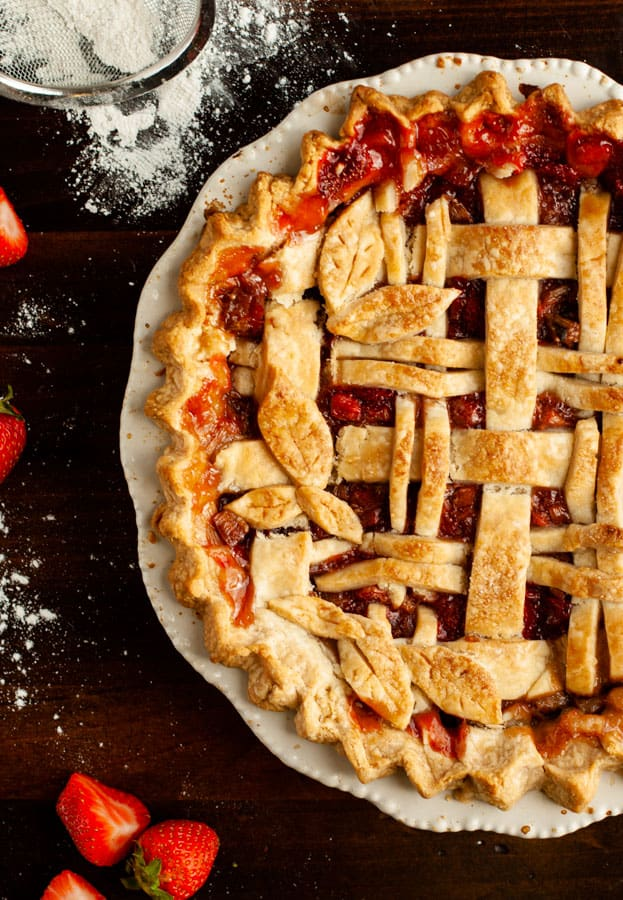 Gluten Free Strawberry Rhubarb Pie surrounded by ingredients, on wooden surface