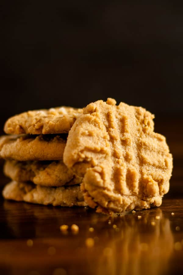 Gluten Free Peanut Butter Cookies in a stack with featured cookie leaning along side