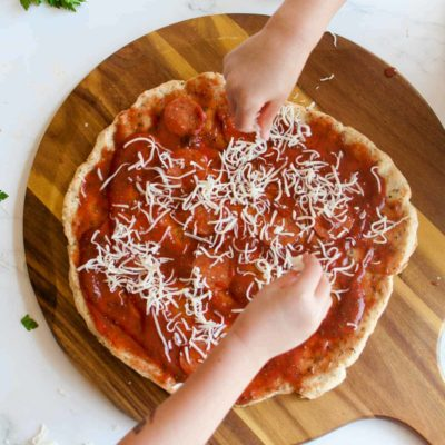 Gluten Free No Yeast Pizza Crust with childrens hands in the scene applying toppings