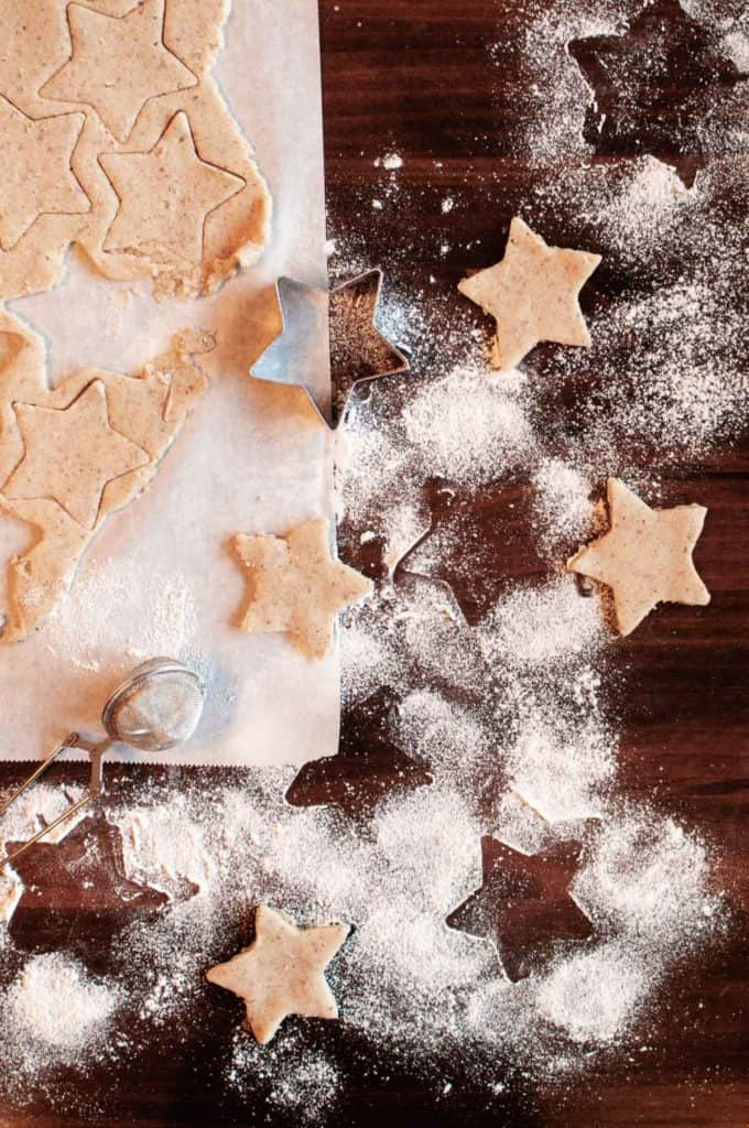 gluten free pecan shortbread cookies being cut out with star shapes surrounded by flour