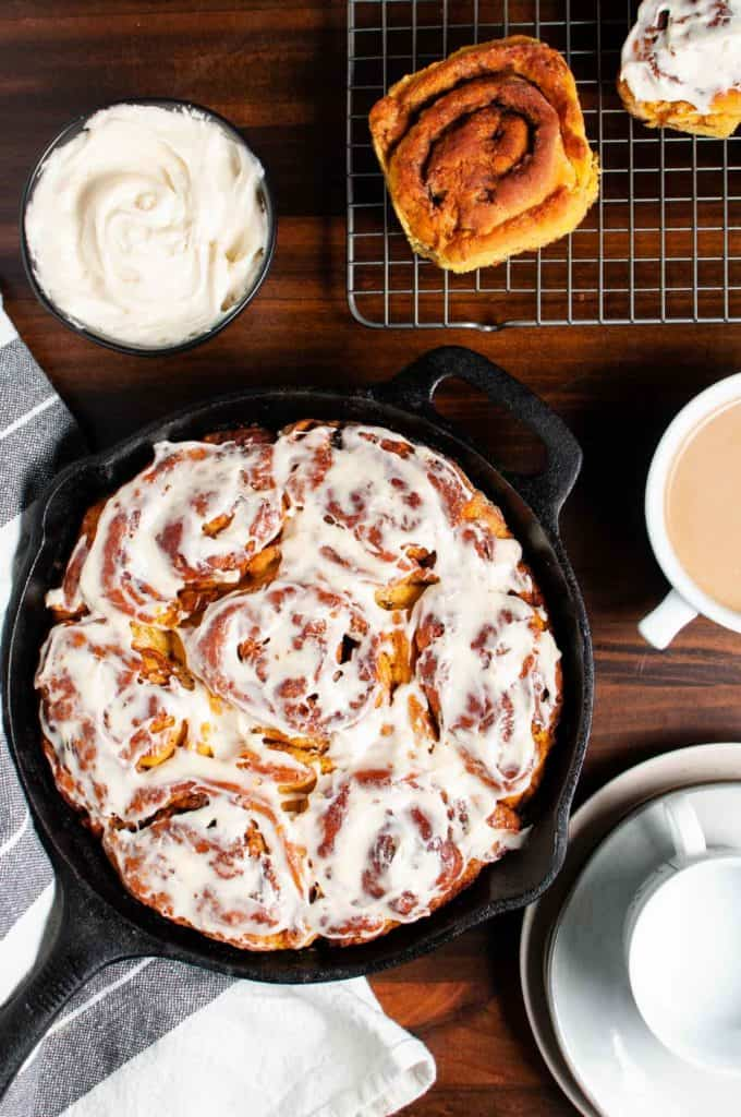 gluten free pumpkin cinnamon rolls displayed in a cast iron skillet ready to serve with coffee