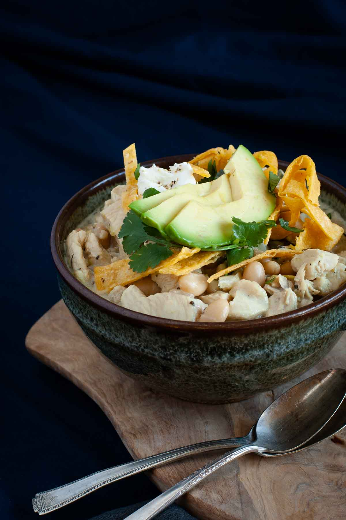 gluten free white chicken chili served in a bowl with avocado and tortilla strips
