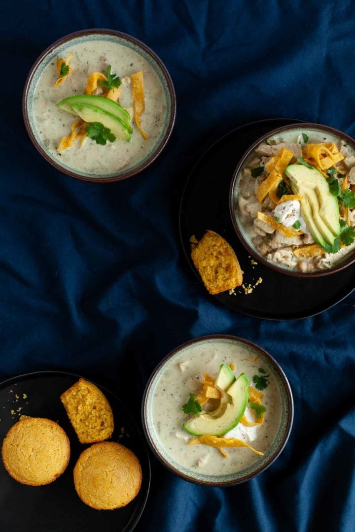 3 bowls of white chicken chili topped with avocado and tortilla strips, served with cornbread muffins