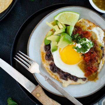 easy huevos rancheros on ceramic plate ready to eat and topped with salsas, avocado and lime