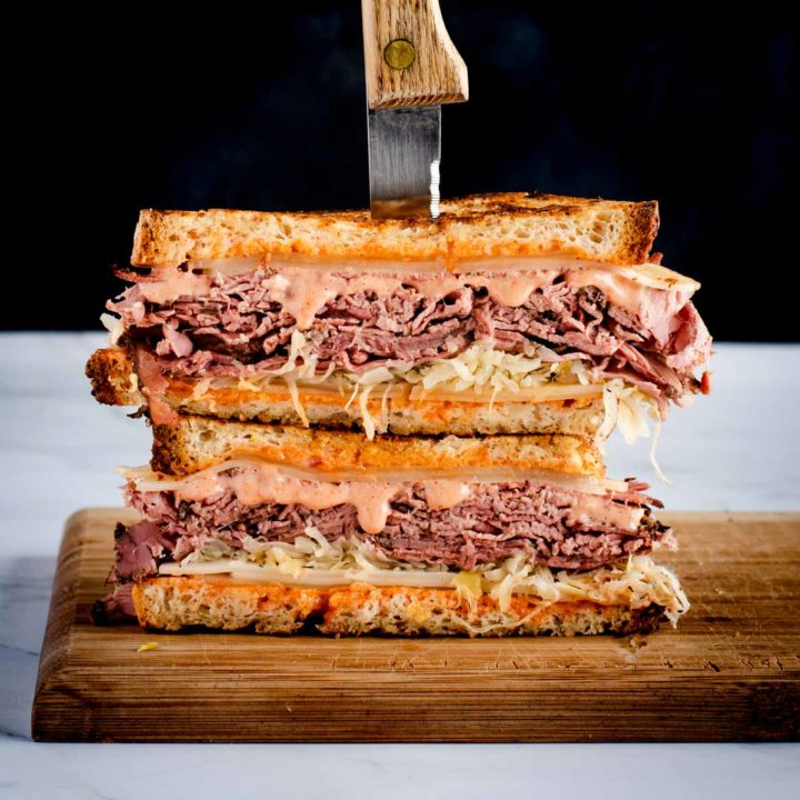 two stacked halves of reuben sandwich displayed for recipe card featured image