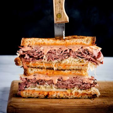 corned beef sandwich with russian dressing displayed on a cutting board, two stacked halves with a steak knife through them.