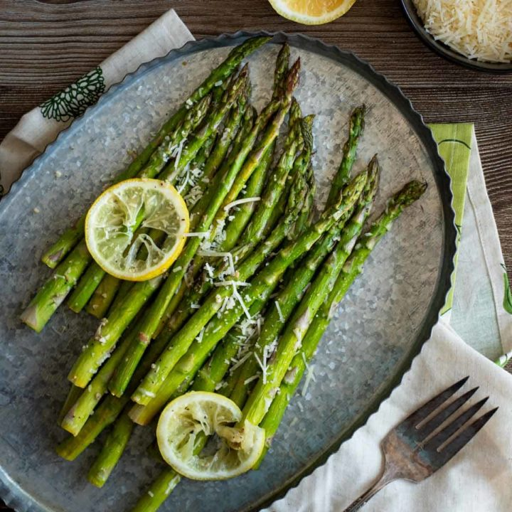 Roasted asparagus on tin serving tray with lemon slices and parmesan