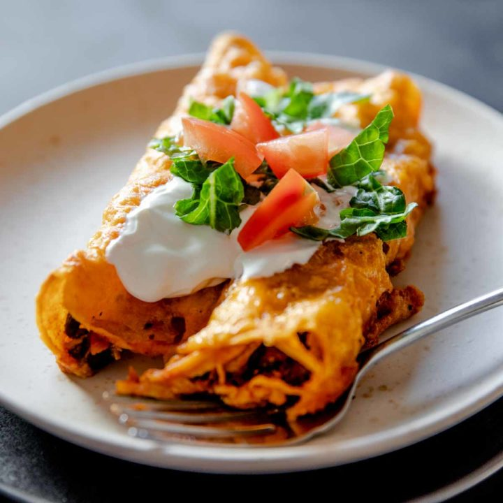individual serving of gluten free chicken enchiladas cooked and served with sour cream, lettuce and tomato