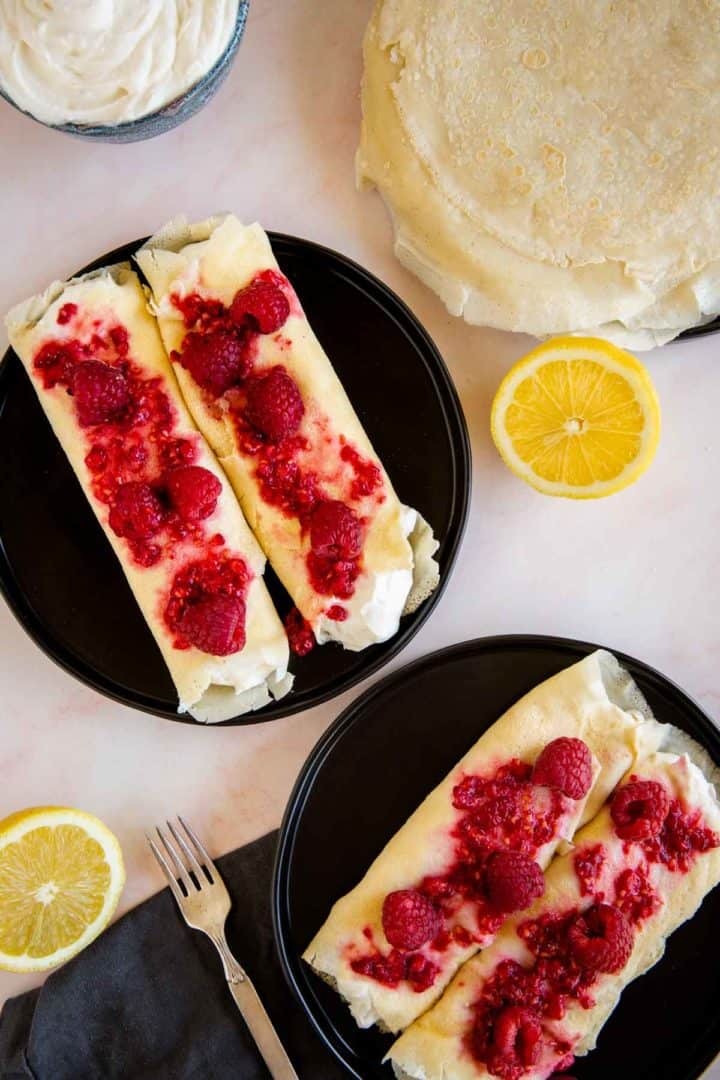 2 servings of ricotta cheese filled blintzes topped with fresh raspberries. Served on black plates on a pink marble surface