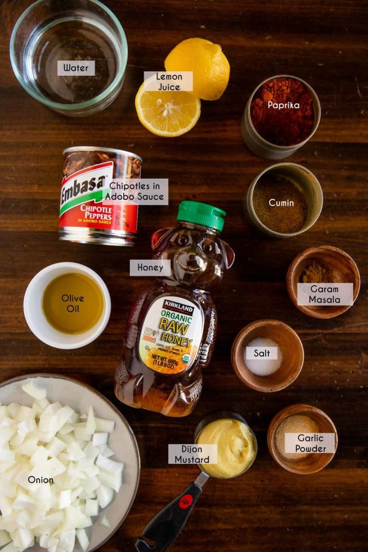 Ingredients needed to make chipotle barbecue sauce laid out and displayed on wooden table