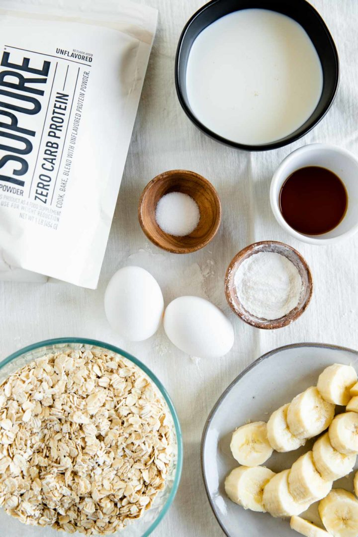 ingredients needed for flourless banana pancakes laid out in dishes displayed on a tablecloth