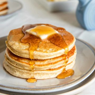 fluffy pancakes on a ceramic plate with a butter pat and syrup drips