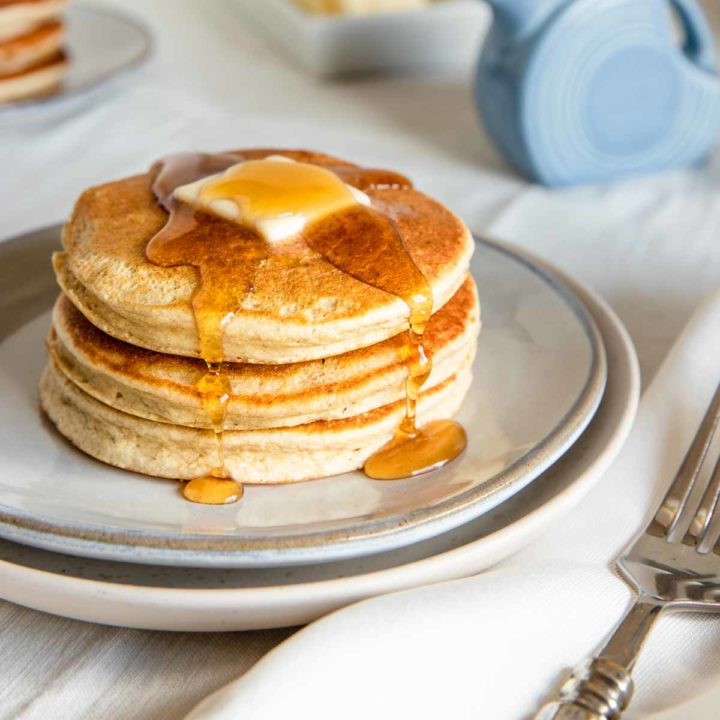 banana pancakes with a butter pat and syrup dripping