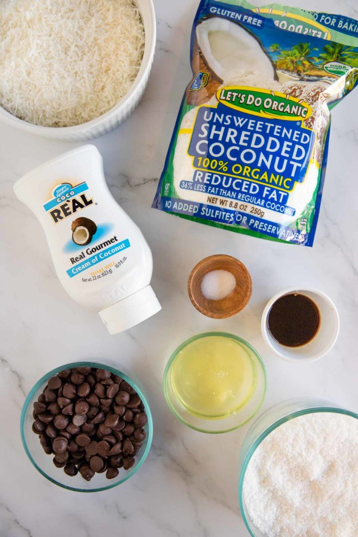 Image of ingredients needed for making coconut macaroons displayed in bowls on a marble surface