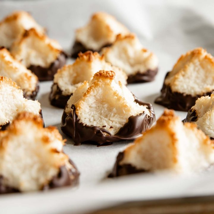 recipe card featured mage of coconut macaroons sitting on parchment and dipped in chocolate