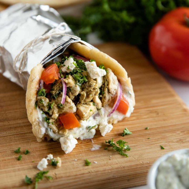 chicken gyro wrapped in foil and ready to eat, sitting on a cutting board and surrounded by fresh ingredients.