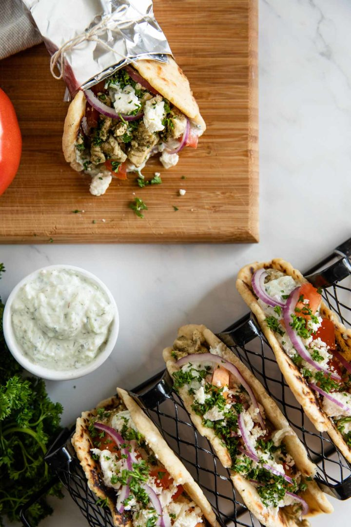 four chicken gyros displayed in a taco rack and ready to eat, surrounded by ingredients