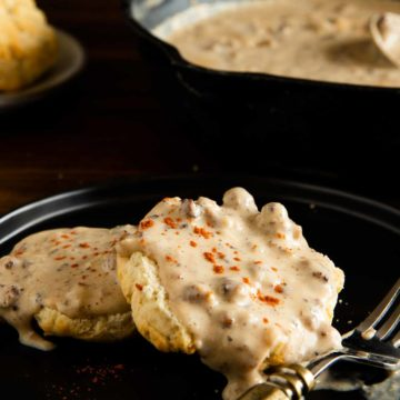 gluten free sausage gravy served over a biscuit and served on a black plate with a sprinkle of paprika