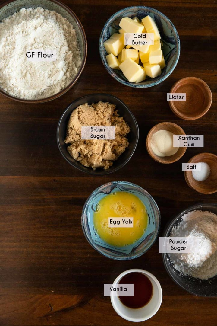 Image of ingredients needed to make a shortbread tart crust laid out in dishes on a wooden surface