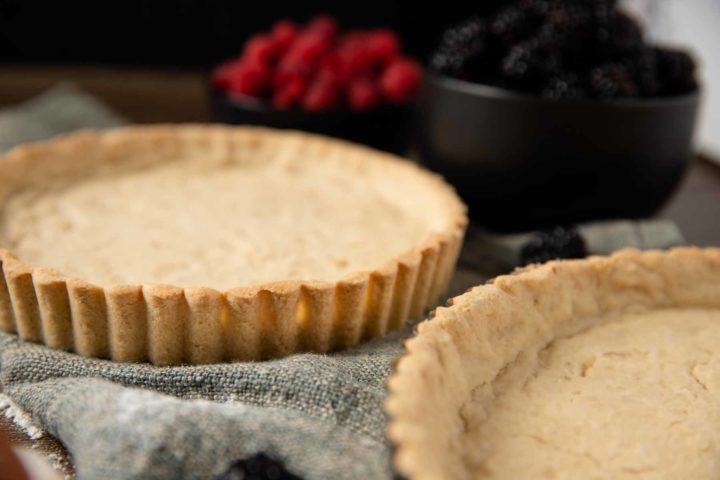 gluten free tart crust baked and ready to be filled, surrounded by berries