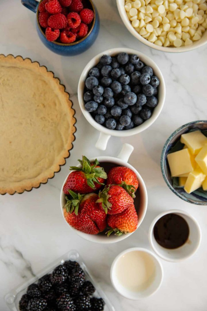ingredients needed for white chocolate berry tart laid out on a white marble surface
