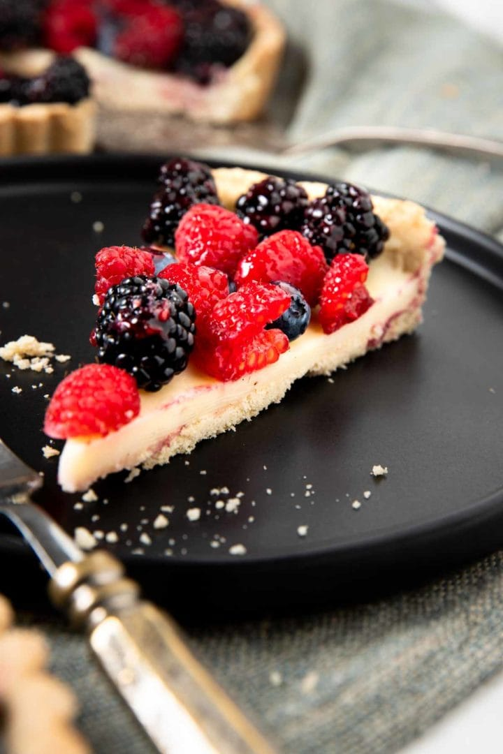 Slice of white chocolate berry tart featuring raspberries and blackberries served on a black dessert plate