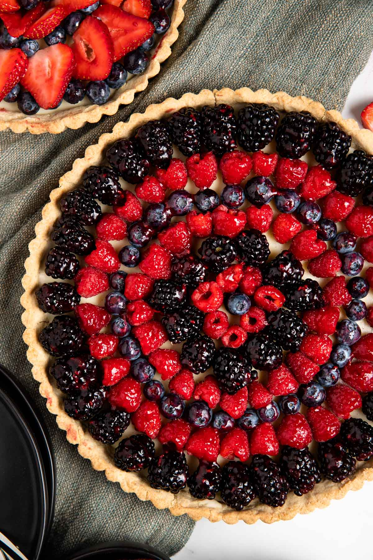 featured image of white chocolate berry tarts with different berry options. Large tart featuring circles of raspberries, and blackberries, smaller tart featuring spirals of strawberries and blueberries