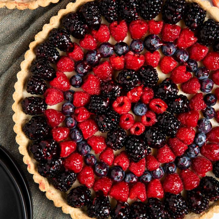 white chocolate berry tart finished with raspberries, blackberries, and blueberries and a jam glaze