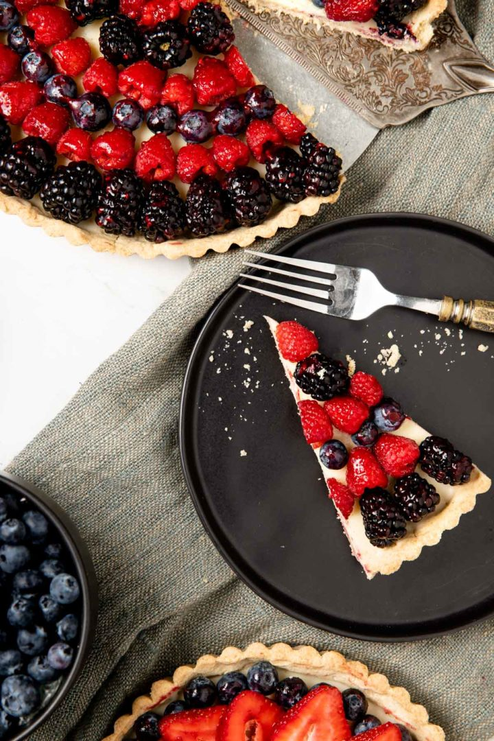 Mixed berry tart with a slice taken out and displayed on a black plate, surrounded by fresh berries