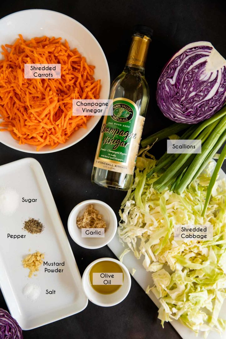 Ingredients needed for sweet and tangy coleslaw laid out on a black surface
