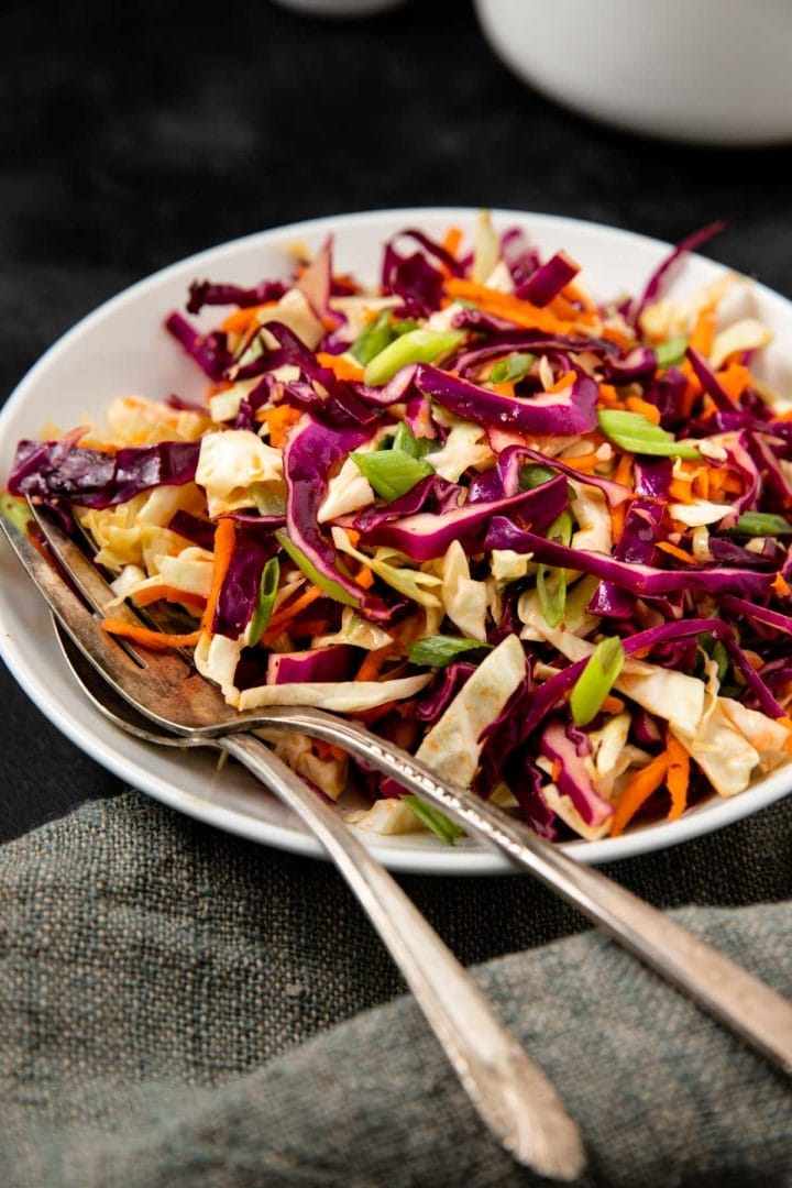 sweet and tangy coleslaw on black background served in a white serving bowl with silver serving utensils