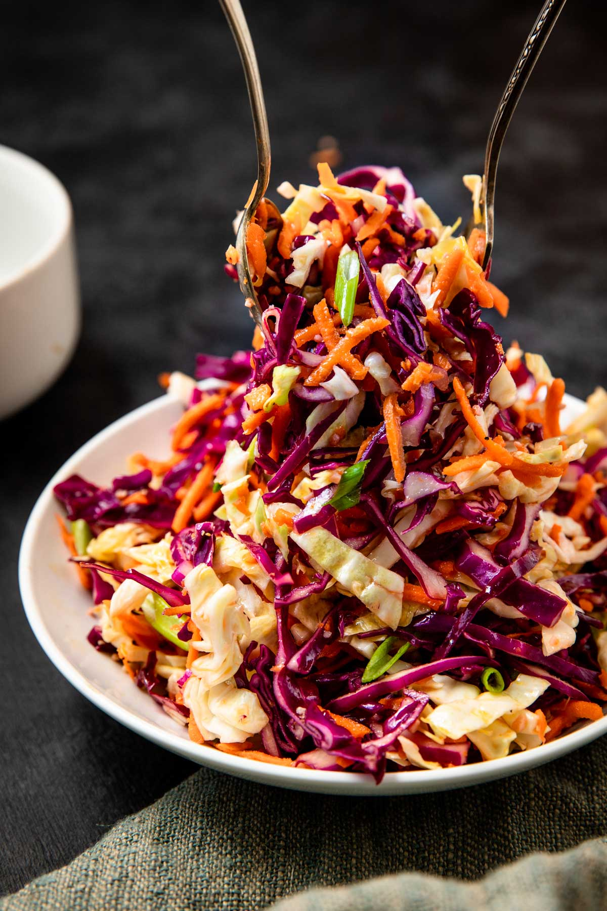 sweet and tangy coleslaw being tossed with serving utensils in a white bowl