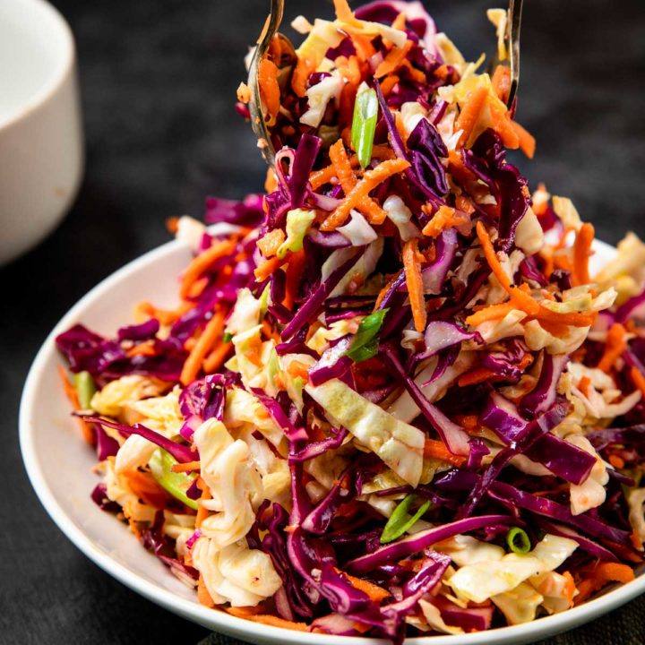 no mayonnaise coleslaw being tossed together in a white bowl