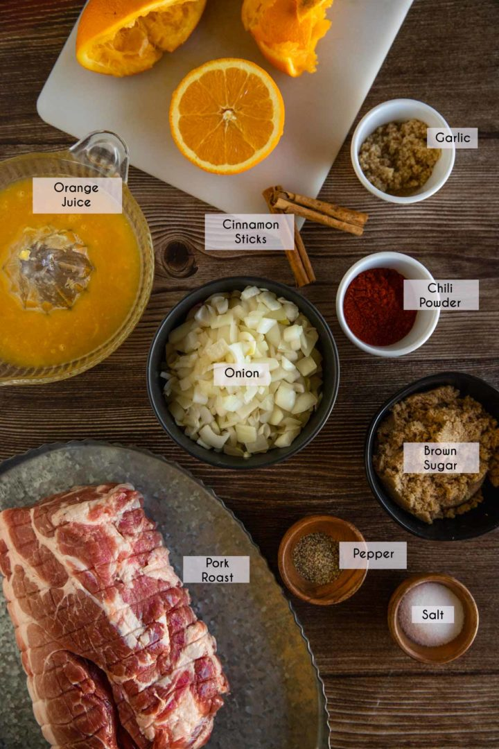 Ingredients needed for homemade pulled pork laid out and displayed on a wooden surface
