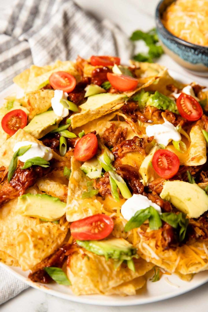 easy shredded pork nachos served on a white plate with toppings