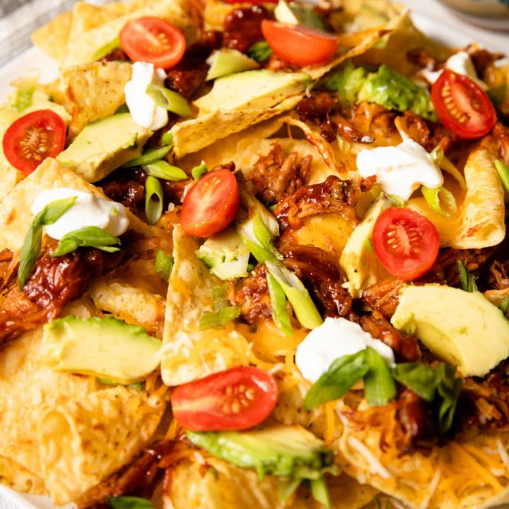 close up of pulled pork nachos served with tomatoes, onion, avocado and sour cream