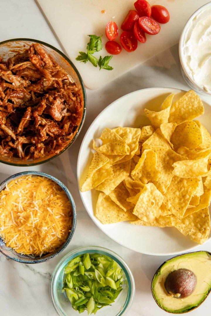 Photo of ingredients needed for shredded pork nachos, chips, pulled pork, shredded cheese and desired toppings