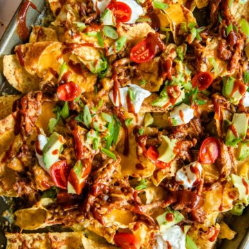 bbq pulled pork nachos fresh from the oven on a baking sheet topped wit toppings